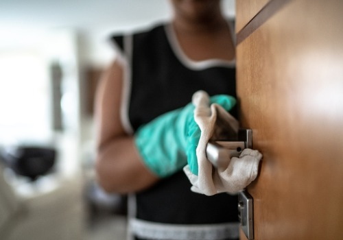 Close Up of Woman Cleaning Door Handle While Performing Janitorial Services for Peoria IL